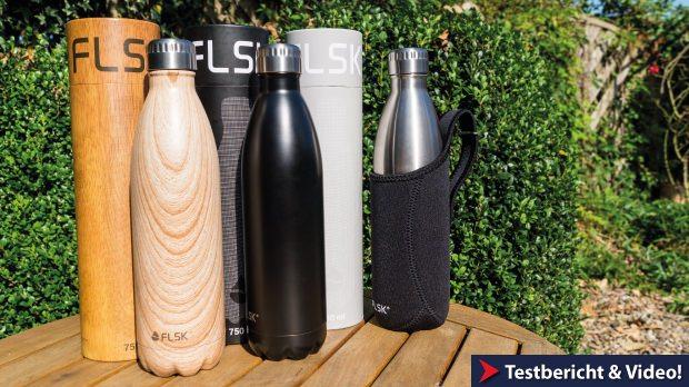 Die Thermosflasche von FLSK in Holzoptik, schwarz und Edelstahl auf einem Tisch.